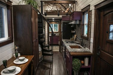spiral tiny house stairs in home with dark wood floors, and cabinets