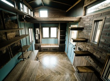 floating tiny house stairs in room with dark wood chevron pattern floors, brick walls, and open shelves