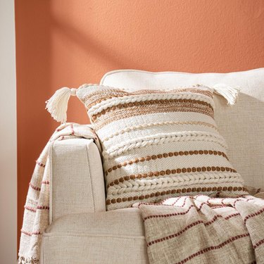 patterned copper pillow on beige couch