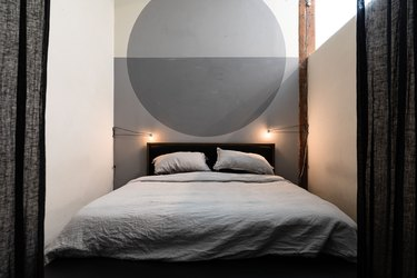 gray calming colors in minimalist bedroom with gray circle accent wall