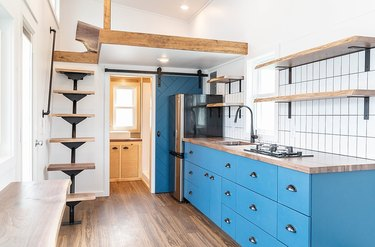 tiny house stairs in small home with blue cabinets, open wood shelves, black finish faucet and hardware, tile backsplash, hardwood floor, wood beams, wood and metal stairs.