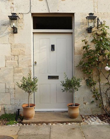 gray front door color with stone exterior