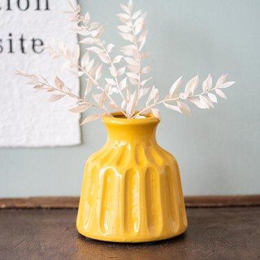 mustard yellow vase with white buds