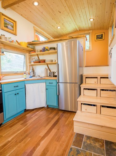 wood tiny house stairs in space with light wood floors, wood ceiling, recess lighting, and blue cabinets.