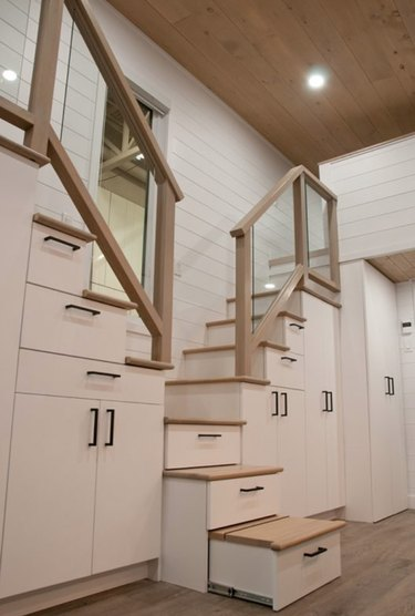 tiny house stairs with white cabinets, light wood floors and hand rails, stairs, wood ceiling, and recessed lighting.