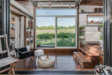 tiny house stairs and dark wood floors, black mid century modern side chair, pouf, sheepskin stool, wood chair, glass sliding door, white subway tile, white cabinets.