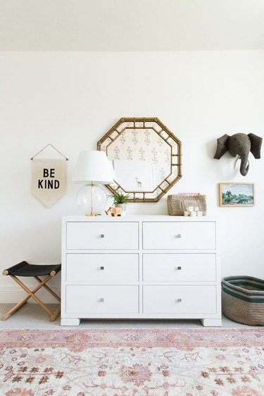 girls bedroom idea with pink area rug and white six drawer dresser