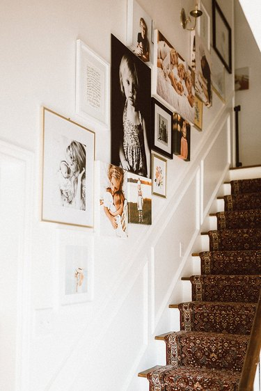 Stairs with carpet runner and gallery wall of family photos