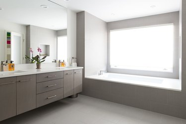 bathroom window with opaque covering and gray double vanity