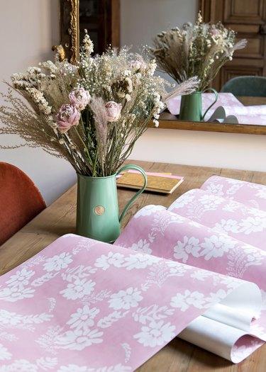 pink wallpaper near vase of flowers