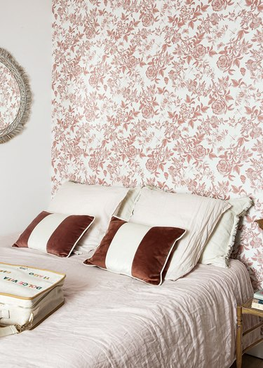 bed with pink wallpaper