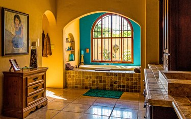 arched bathroom windows with in bathroom with large floor tiles and and drop-in tub