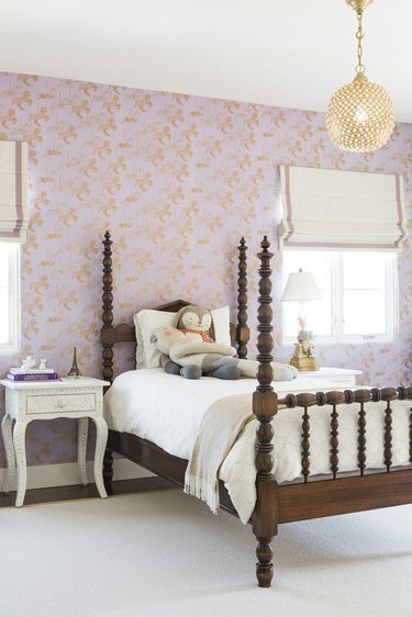 girls bedroom idea with pink patterned wallpaper and four poster bed