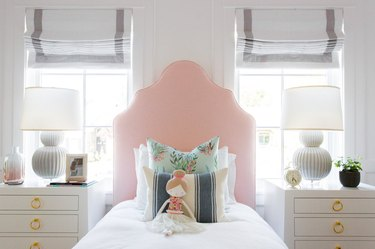girls bedroom idea with pink upholstered headboard and matching nightstands