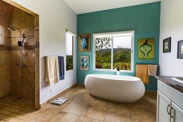 bathroom windows in bathroom with green accent wall and artwork framing window