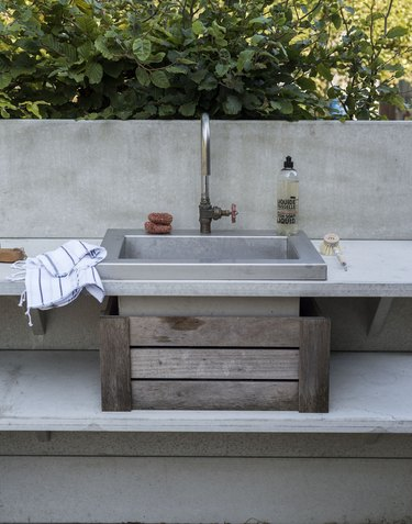 outdoor kitchen idea with concrete countertops and stainless steel sink