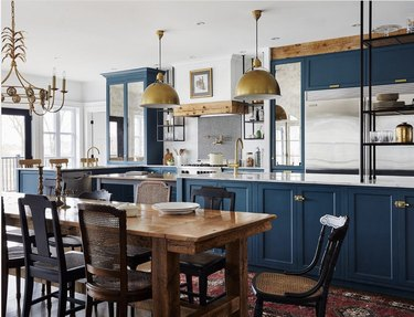 Rustic blue kitchen with wood table and gold pendant lights