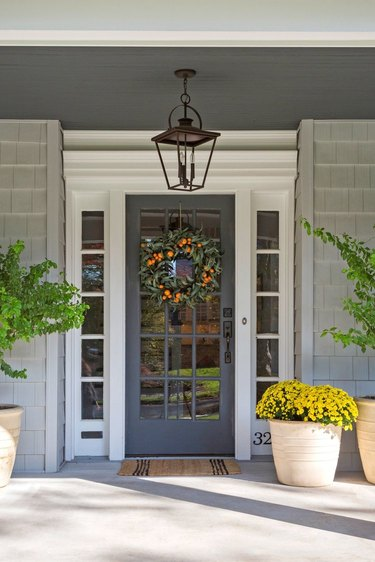 traditional home exterior idea of front porch with plants and a decorative wreath on the door