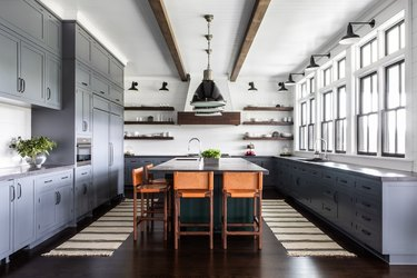 Grey-blue cabinets in a rustic blue kitchen with leather bar chairs