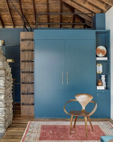 Rustic blue Murphy bed in a cabin with vintage red rug