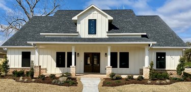 traditional home exterior idea of white house with accent lighting on the front porch