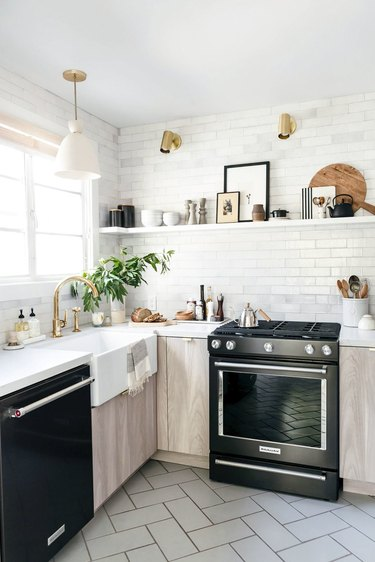 Modern farmhouse kitchen with black range, dishwasher, light wood cabinets, subway tiles, open shelf