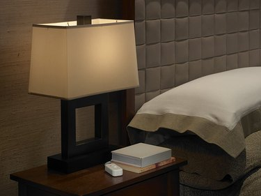 Bedside lamp with dimmer next to modern upholstered headboard