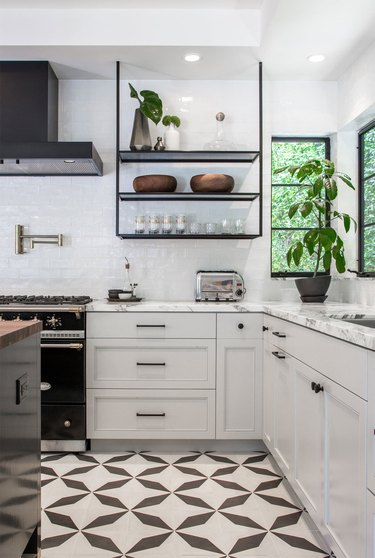 Black and white kitchen floor tile idea with white cabinets and black hardware