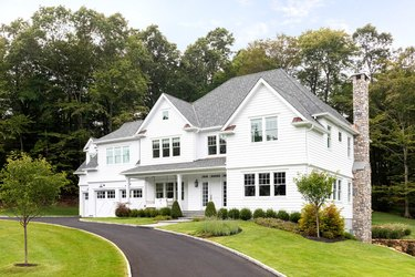 traditional home exterior idea with large white house surrounded by trees.