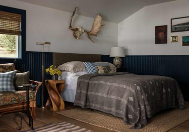 Rustic blue wainscoting in bedroom with antlers above bed