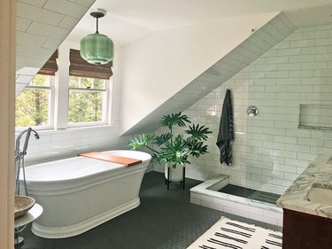bathroom window with natural wood shades and arched shower with subway tile