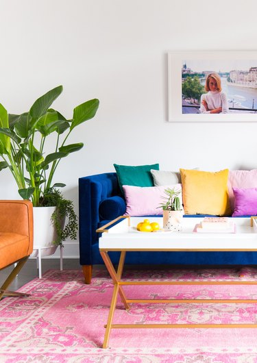 cool white living room makeover idea with pink rug and colorful sofa