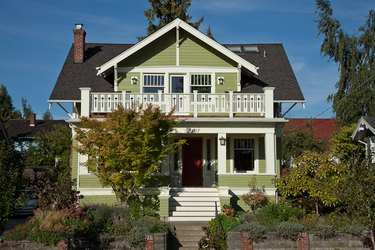 traditional home exterior idea of green house with red accent door