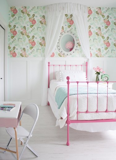 girls bedroom idea with pink bed frame and green patterned wallpaper above white wainscoting