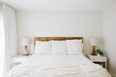 minimalist small bedroom decorating idea with wood headboard and white nightstands