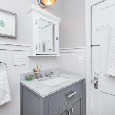 Bathroom organization idea with marble countertop and gray vanity cabinet