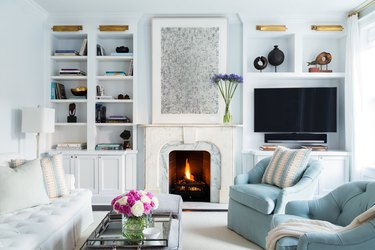 Formal living room TV idea with bookcase and fireplace