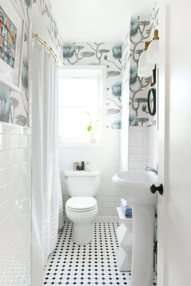 small bathroom organization idea with mosaic tile floor and subway tile wainscoting with patterned wallpaper above