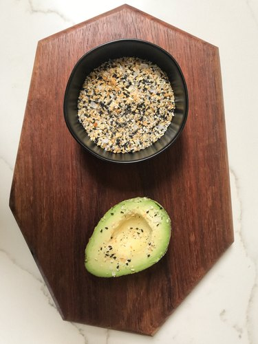 Wood board with spices in black bowl and avocado