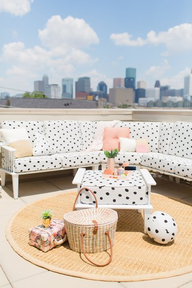 rooftop outdoor patio seating area with sectional sofa and round area rug