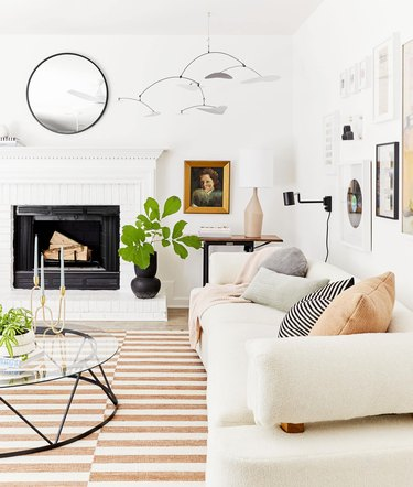 white living room with striped rug and traditional fireplace, white sofa, coffee table