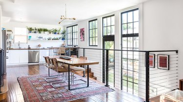 Modern dining room with boho rug and kitchen