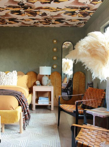 maximalist bedroom with earth tone palette and wallpaper on ceiling