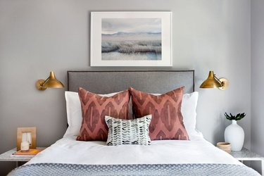 Small bedroom decorating idea with brass wall sconces and upholstered headboard