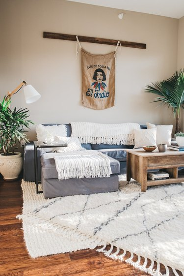 White bohemian living room idea with wall hanging and layered rugs