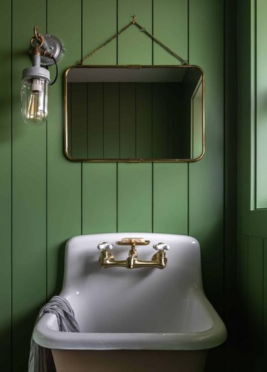Moss green shiplap walls, vintage mirror, sconce, sink, brass faucet in bathroom with rustic colors