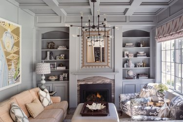 gray living room with traditional fireplace and ornate mirror and chandelier