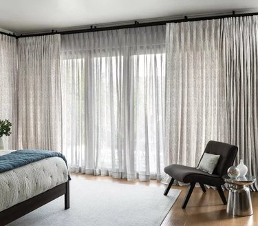 window treatments for sliding glass doors in minimal bedroom with rug and gray side chair