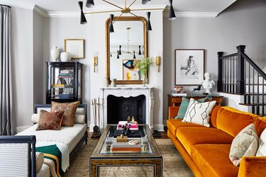 elegant living room with ornate traditional fireplace and mirror on top, orange sofa, white daybed