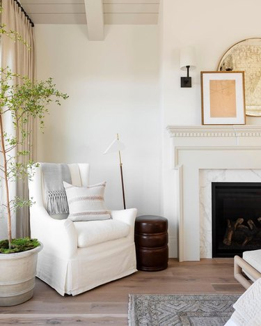 beige room with traditional fireplace and white armchair
